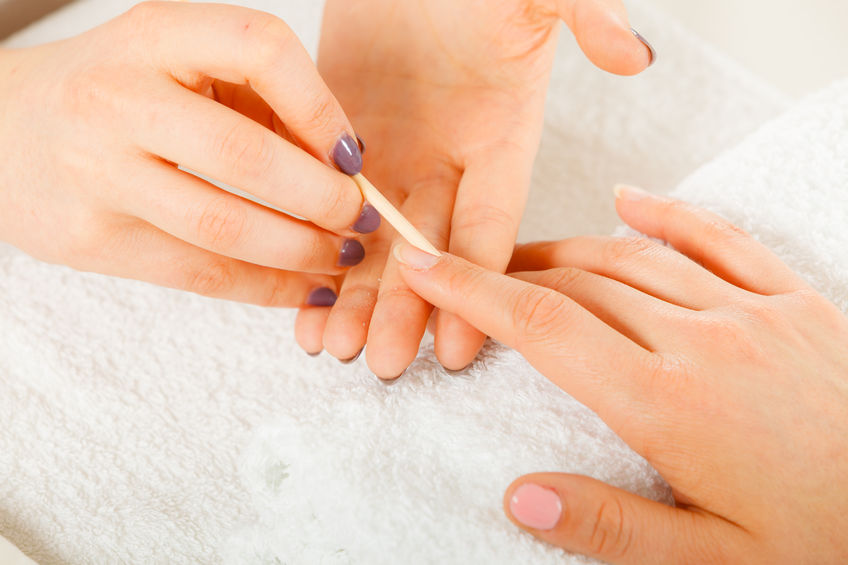 90103128 - nail care, beauty wellness spa treatment concept. woman beautician preparing nails before manicure, pushing back cuticles using wooden stick
